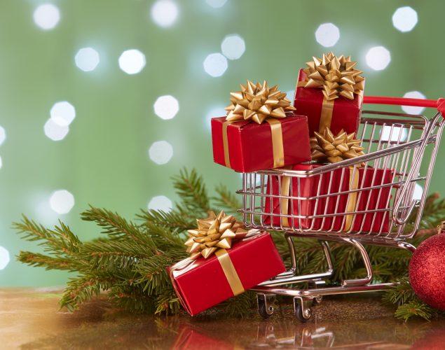 Carrito de compras con cajas de regalos y ramas de árbol navideño. concept: marketing