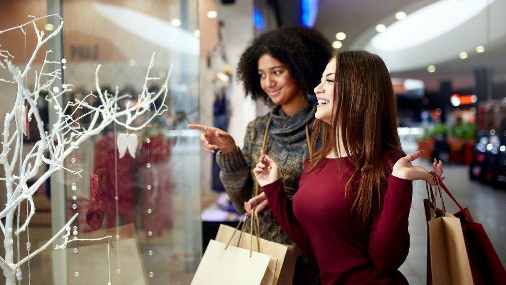 Young multiethnic diverse race women with paper shopping bags near decorated shopwindow. Girl pointing by finger at shopfront, clothes and products in mall on christmas new year sale. Black friday. concept: marketing ideas