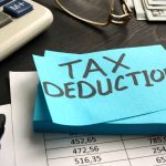 Tax deduction written on a piece of paper. Concept: is a business loan tax deductible?