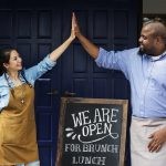 Cheerful business partnership owners standing with open sign blackboard