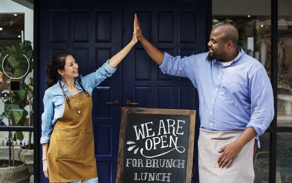 Dueños de una asociación comercial celebrando apertura a la puerta de su restaurante