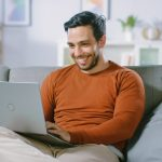 Cheerful Young Man Sitting on a Sofa Holds Laptop on His Lap, Browses Through the Internet, Social Networks, Does e-Shopping. Man at Home Using Laptop while Sitting on a Couch. concept: small business website