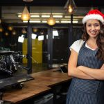 Restaurant owner wearing santa hat. Concept: Restaurant work-life balance during the holiday season