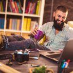 Joven trabajando desde casa en su latop tomando un café. concept: negocios desde casa