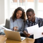 Serious African American couple discussing paper documents, sitting together on couch at home, man and woman checking bills, bank account balance, terms of contract, mortgage, loan agreement. concept: Business Loan Marketplace