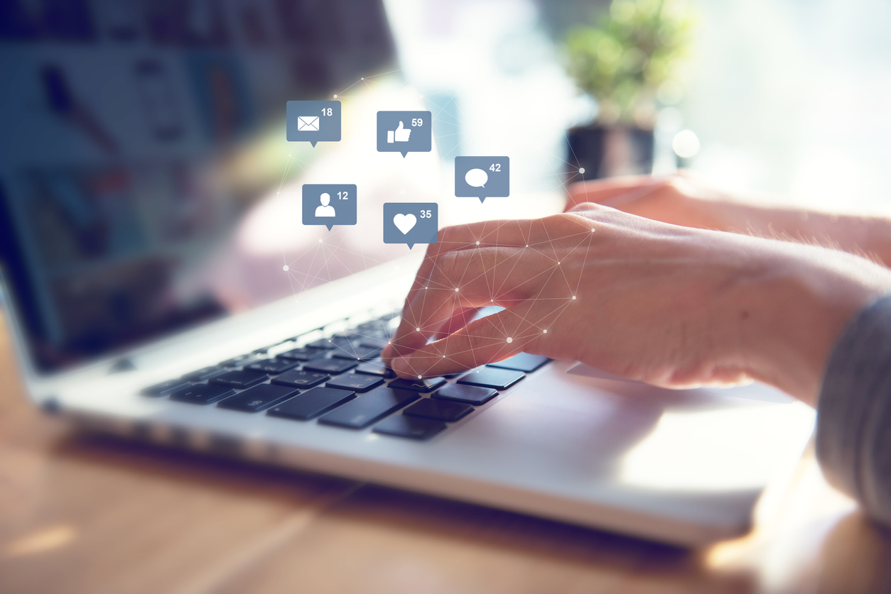 Businesswoman hands using laptop with icon social media and social network, Marketing. Concept: How to Post a Job on Facebook