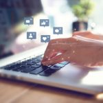 Manos de una empresaria usando laptop con iconos de redes sociales. concept: publicar vacante