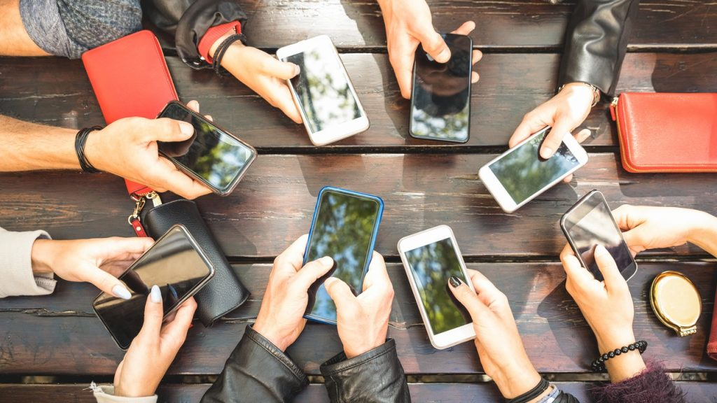 People group having addicted fun together using smartphones - Detail of hands sharing content on social network with mobile smart phones - Technology concept with millennials online with cellphones. concept: how to boost a post on facebook