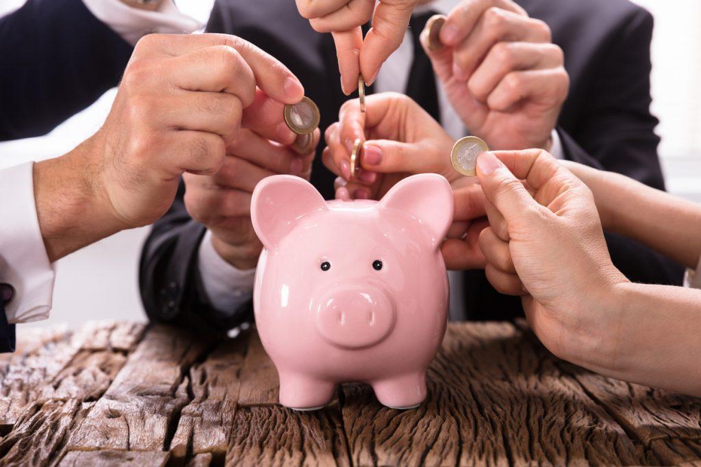 Crowdfunding Concept. People Inserting coins into piggybank. concept: Indiegogo vs Kickstarter