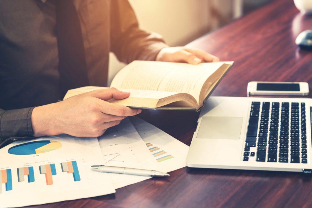 Persona de negocios leyendo un libro en su oficina. concept: libros de contabildiad