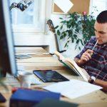 Hombre sentado en su oficina nleyendo un libro. concept: libros de marketing