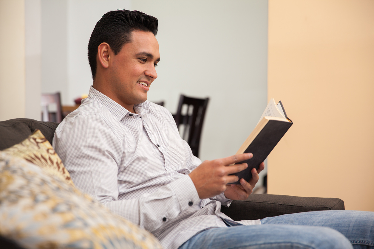Handsome guy relaxing and reading a book at home. Concept: Best Entrepreneur Books