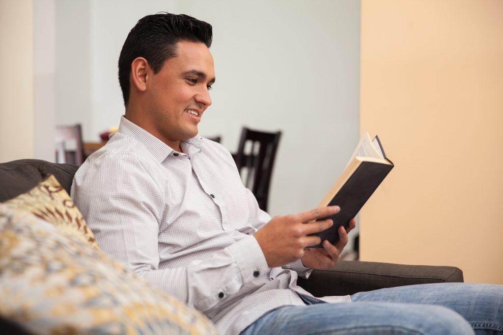 Hombre latino relajándose en casa leyendo un libro. Concept: libros para emprendedores