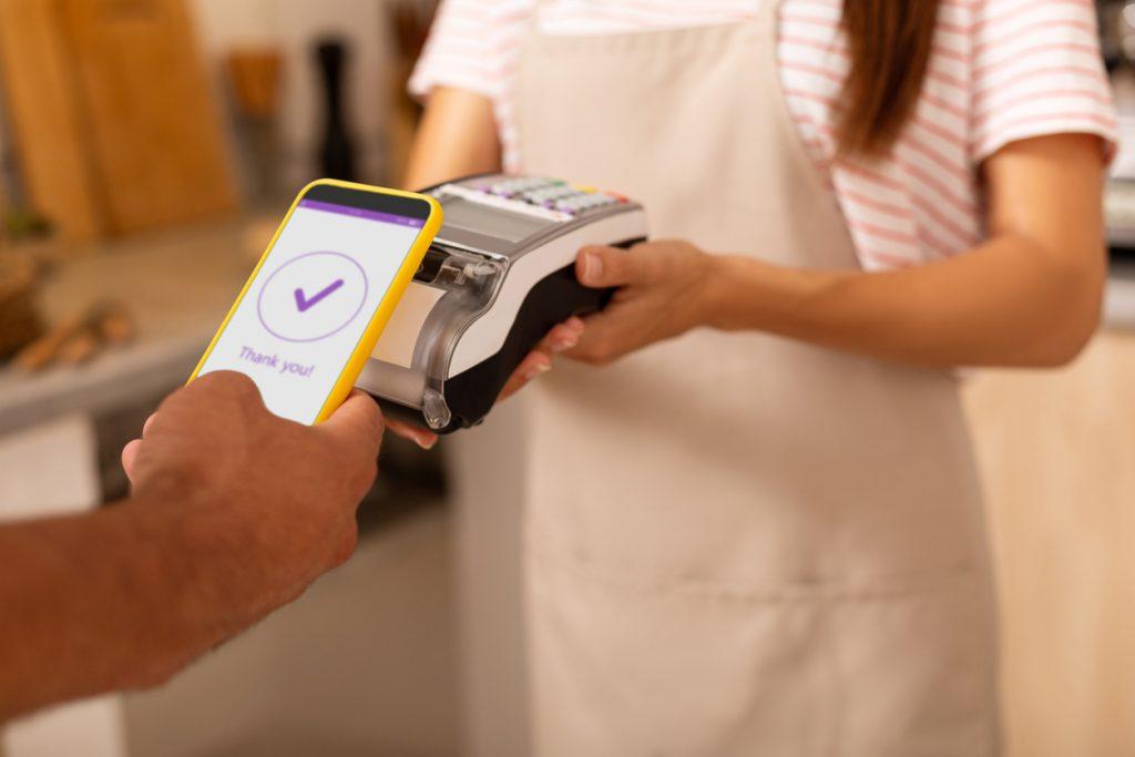 Pago con celilcar. Persona pagando servicios con su celular. Concept: square o paypal