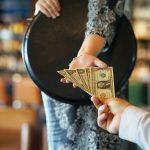 Mesera aceptando pago en efectivo de cliente. Concepto: Consejos para aumentar el flujo de efectivo de tu restaurante.