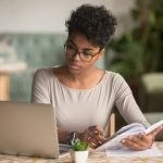 Focused young african american businesswoman or student looking at laptop holding book learning, serious black woman working or studying with computer doing research or preparing for exam online. Concept: Best Entrepreneur Books for Women