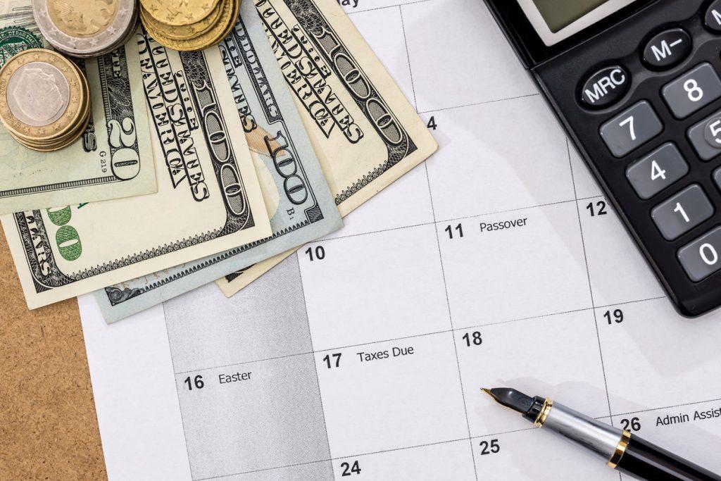 Calendario con fecha para pagar, dólares y monedas. Concept: pagos recurrentes