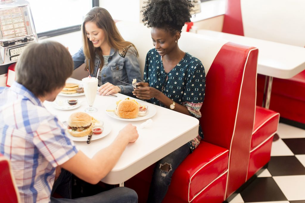 Group of friends eating hamburguers in a diner. Concept: restaurant franchises.