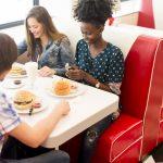 Amigos comiendo hamburguesas en una franquicia de restaurantes.