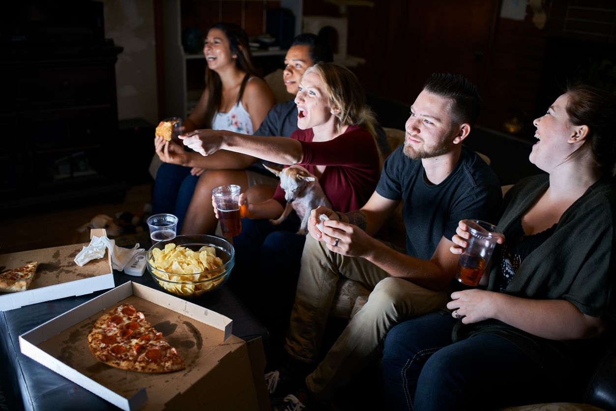 Group of friends watching the best business movies and eating popcorn and pizza.