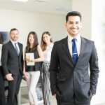 Handsome young CEO leading multiethnic team in office. concept: business magazines