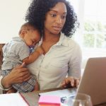 Mother With Baby Working In Office At Home Looking At Laptop. Concept: business ideas for mompreneurs