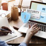 Mujer sentada frente a computadora con icono de seguridad. Concepto: seguros contra ataques cibernéticos.