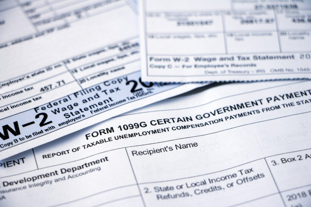 Closeup of overlapping Form 1099G Certain Government Payouts and W-2 forms. Concept: w2 vs w4