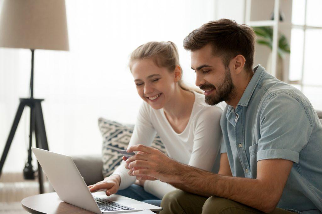 Pareja casada en su sala en casa haciendo pagos por internet con su tarjeta. Concept: pagos recurrentes