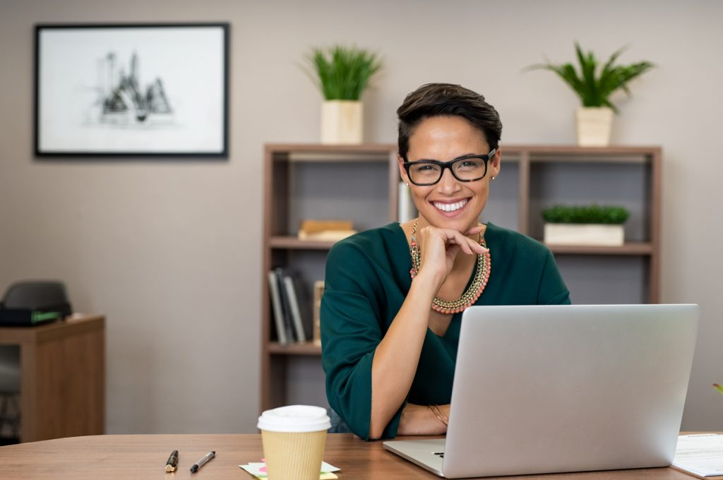 Portrait of happy casual businesswoman sitting at her desk in office. Cheerful latin woman working on laptop and looking at camera. Young fashionable girl wearing eyeglasses sitting at creative agency. Concept: business terms