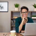 Retrato de mujer de negocios sonriendo, sentada frente a un escritorio en su oficina. Concept: términos empresariales