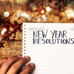 Person writing new year resolutions first person view. Concept: New Year's Resolutions