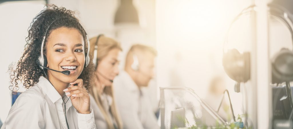 Call center worker accompanied by her team. Smiling customer support operator at work. Young employee working with a headset. concept: best buy for business