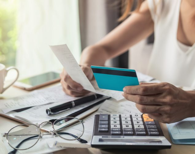 Young woman checking bills, taxes, bank account balance and calculating credit card expenses at home. concept: Cost of Debt Formula