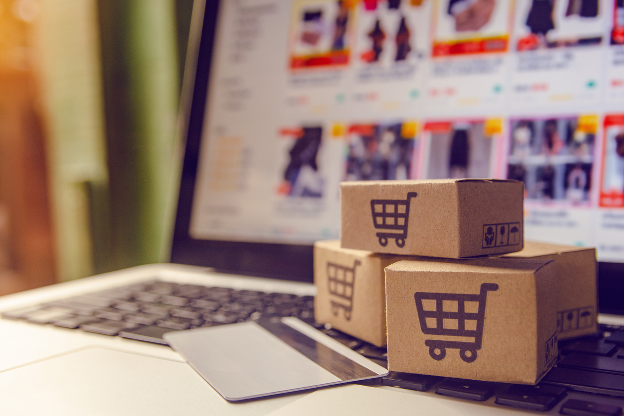 Shopping online concept - Shopping service on The online web. with payment by credit card and offers home delivery. parcel or Paper cartons with a shopping cart logo on a laptop keyboard. concept: Shopify vs Amazon