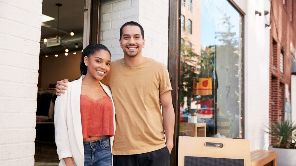 Young Hispanic couple smiling to camera outside their shop. concept: square vs paypal