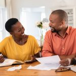 Cheerful mature couple sitting and managing expenses at home. Happy african man and woman paying bills together and managing budget. Black smiling couple checking accountancy and bills while looking at each other. concept: What Is A UCC Filing