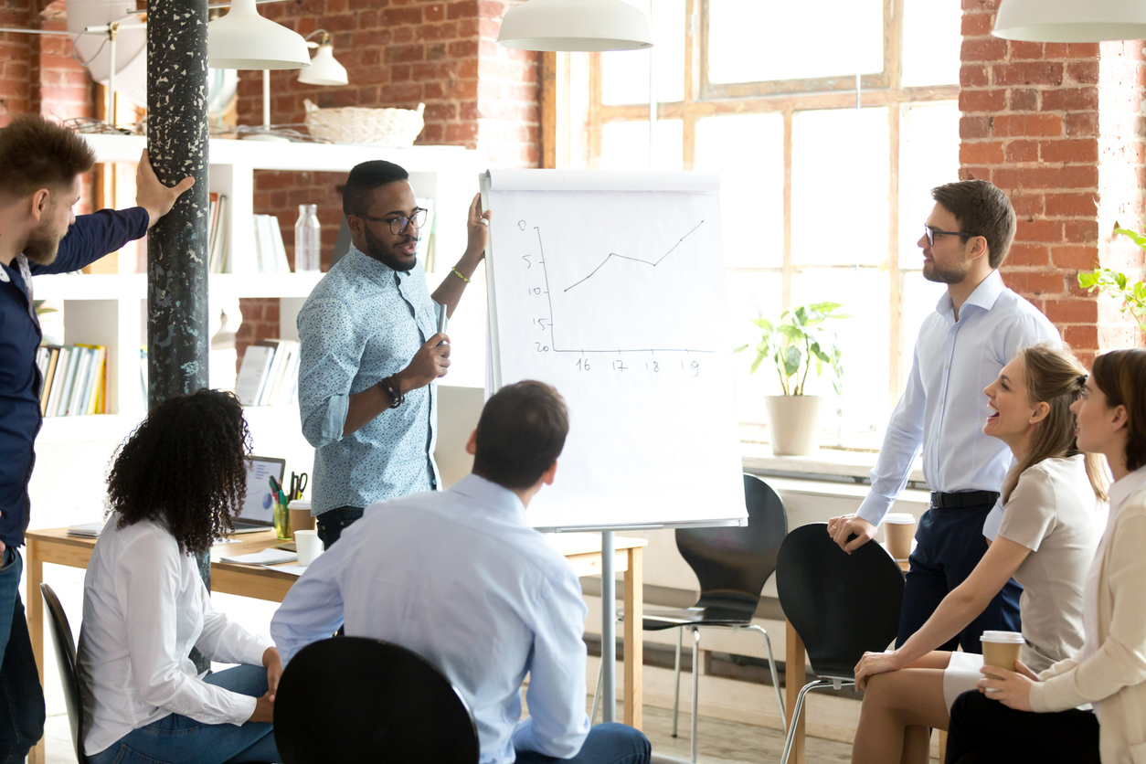 Confident smiling African American business coach speaking presentation to colleagues group at briefing, company meeting, explaining growth of sales graph, reporting about good result, motivating workers. concept: Types of Financial Companies