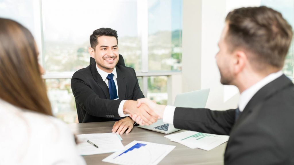 Financial adviser sealing a deal with clients at desk in office. concept: Financial Companies