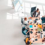 Multiethnic diverse group of business coworkers in team meeting discussion, top view modern office with copy space. Partnership professional teamwork, startup company, or project brainstorm. concept: firma de consultoría