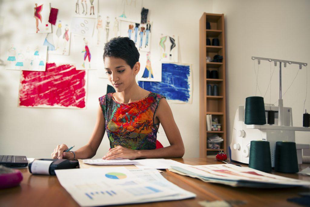 Designer in her studio working on paperwork. Concept: interim financial statements