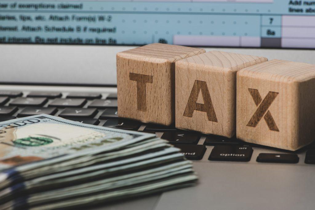 Billetes y computadora. Presentación de impuestos en línea. concept: exacción fiscal