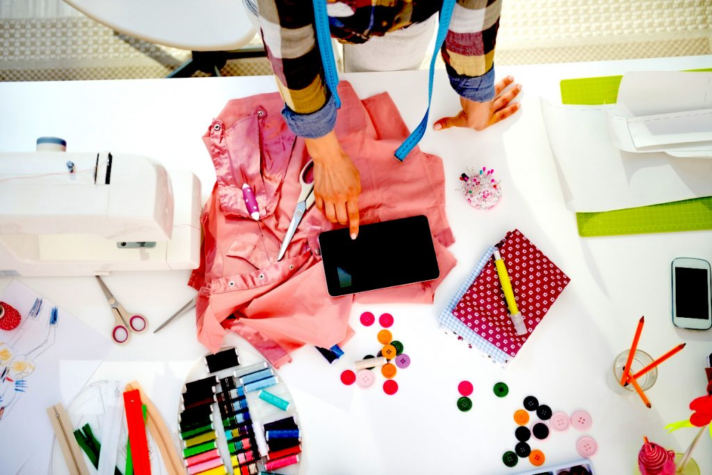 Woman doing crafts and using tablet. Concept: how to sell on Etsy