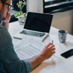 Hombre pensativo concentrado en hacer cuentas de impuestos frente a su laptop. concept: impuestos como trabajador autónomo