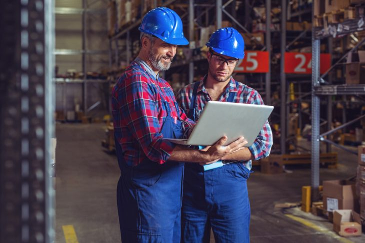 Two business owners in warehouse with laptop. Concept: Profitability ratios