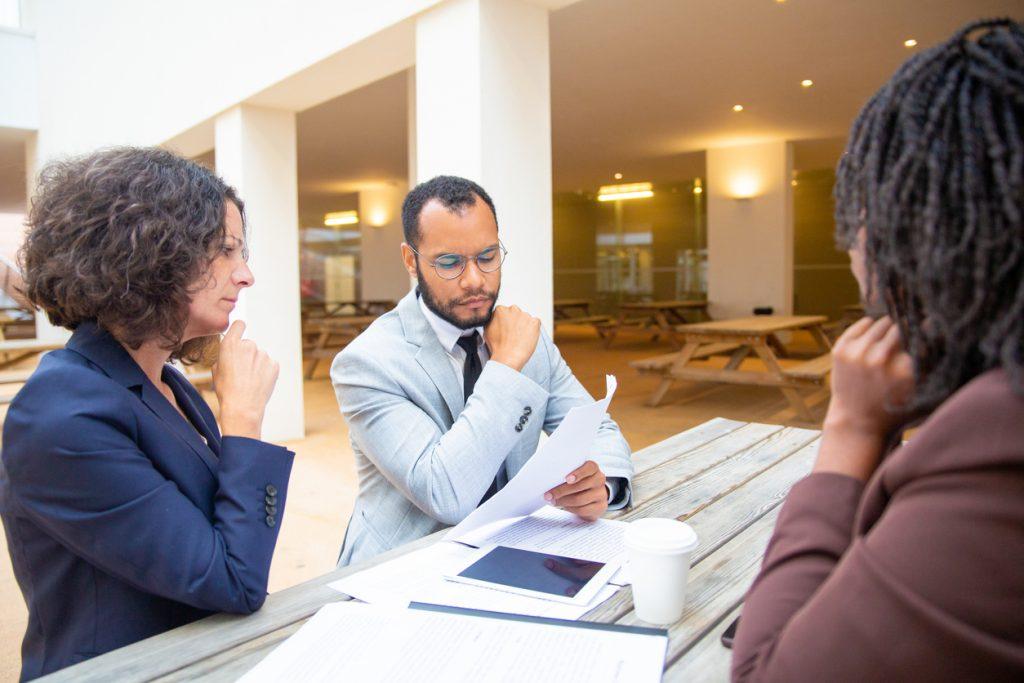 Dueños de un negocio concentrados leyendo un contrado. concept: acuerdo de compraventa de acciones