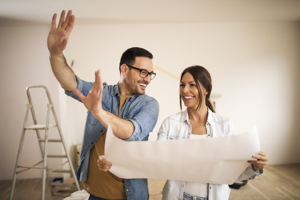 Young couple standing in their apartment while woman holding blueprint and man showing to her new ideas. Concept: personal loan