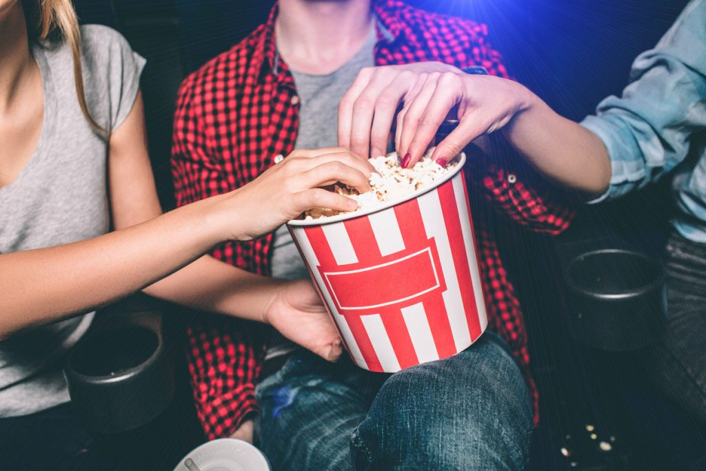 Close up of red with white basket of popcorn that both girl and guy are holding.