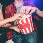 Primer plano de bolsa de palomitas de maíz y tres personas en el cine. Concepto: Las mejores películas para dueños de restaurantes.