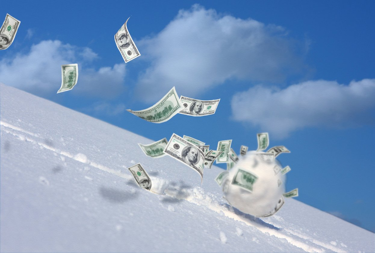 snowball rolling down and picking up dollar bills. Concept: the snowball method to pay off debt